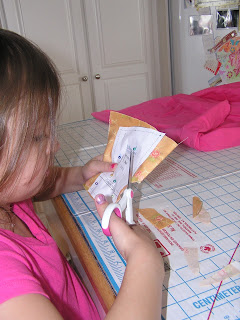 Child cuting out a sewing pattern