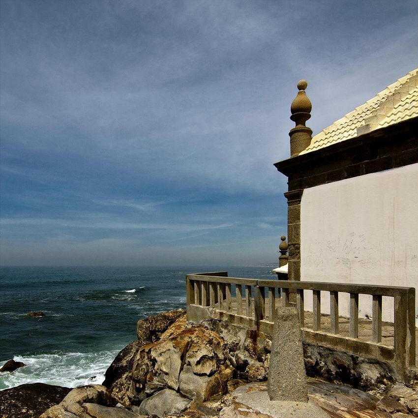 Foto do varandim da capela, com o mar à esquerda, as rochas em primeiro plano e à direita uma parte da capela
