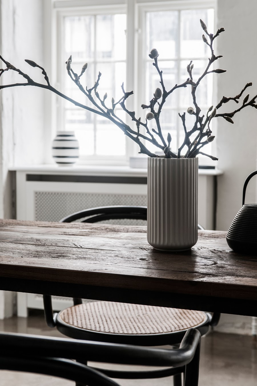 twigs branches in vase on dining room table small apartment