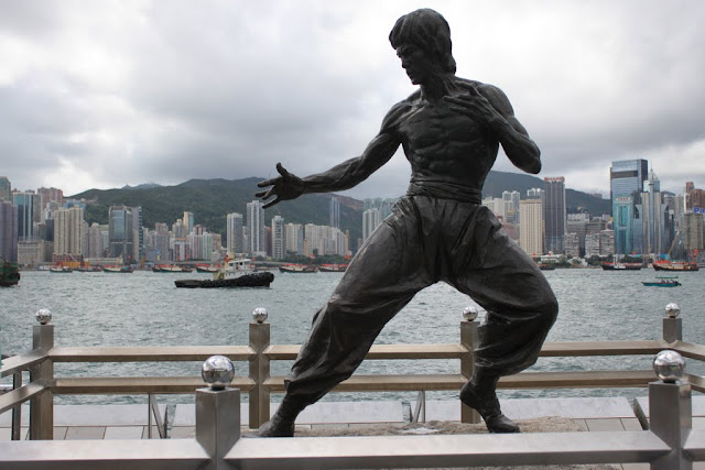 The statue of Bruce Lee at Avenue of Stars with famous skyscrapers along Victoria Harbour in Hong Kong