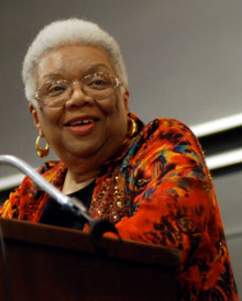 Smiling Lucille Clifton in bright dress at a podium