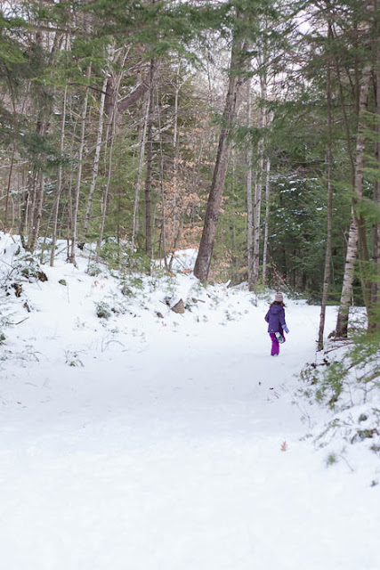 little girl running away in the snowy woods
