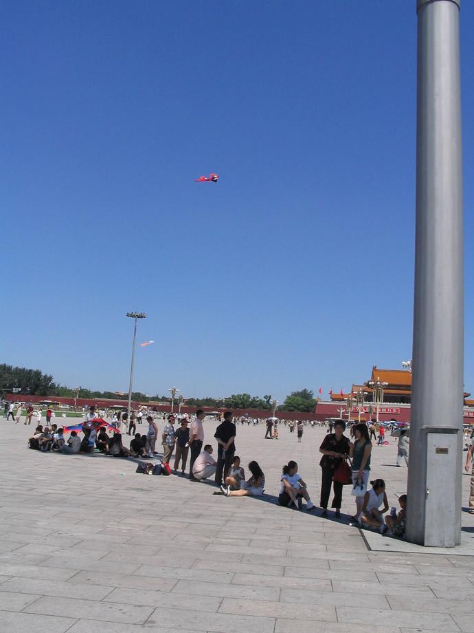 Pessoas se protegem do sol em sombra de poste