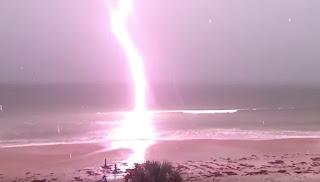 A powerful lighting bolts near the shore.