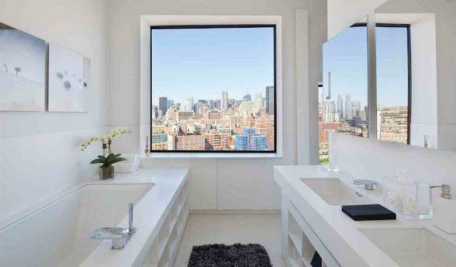 white master bedroom with built in tub and gray shag rug with a black trimmed window overlooking NYC's skyline