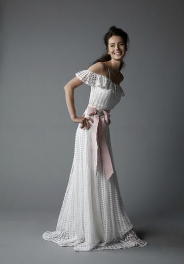 This artisanal hand crochet dress has an off the shoulder flounce and yards