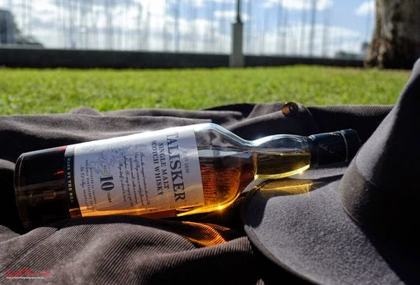Talisker Whisky still life, jacket hat and product photographed in a Sydney Harbour Park, social media marketing and promotion.