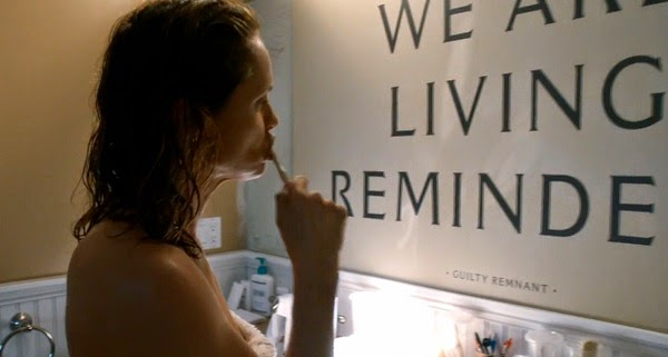 Laurie se lava los dientes frente a un mensaje de su secta