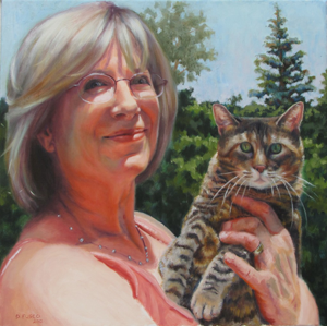 Smiling lady with her pet tabby cat in her arms.