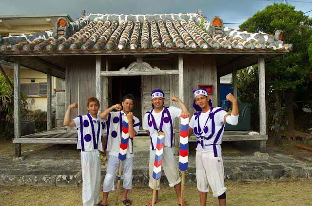 young men in traditional clothing pose at house of a priestess