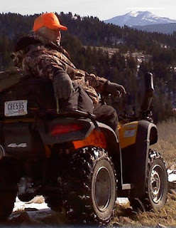 Verl Terry on a four wheeler with his camouflage jacket and hunter orange hat