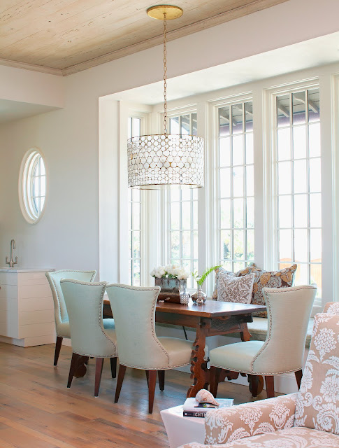 Dining room in a beach house with a serena drum chandelier, large windows, wood floor, upholstered chairs around a vintage wood table