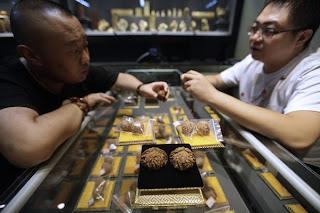 SEORANG pemilik kedai (kanan) menjual beberapa kacang walnut kepada pelanggannya di Pasar Antik Antarabangsa Yayuan di Beijing Ahad lalu.