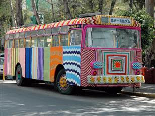city bus completely covered in multicolored crochet