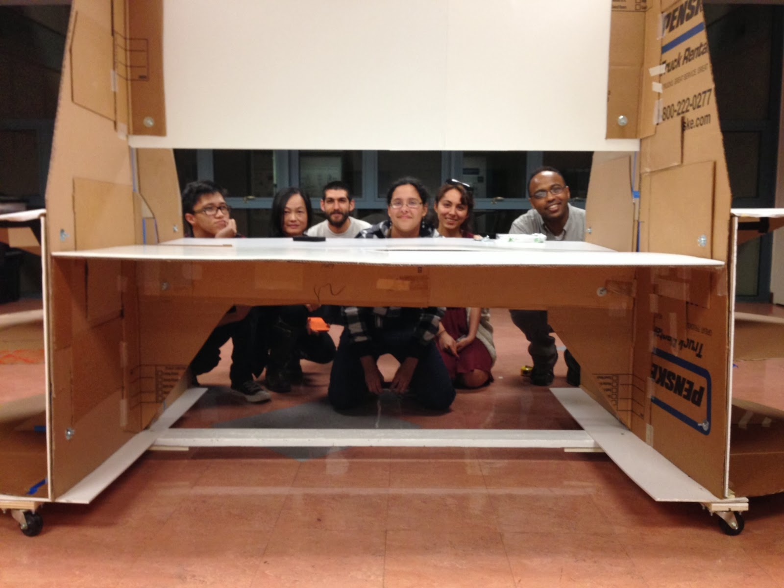 Image shows an opening in the full-scale cardboard prototype with students kneeling and peering through as the picture was taken.