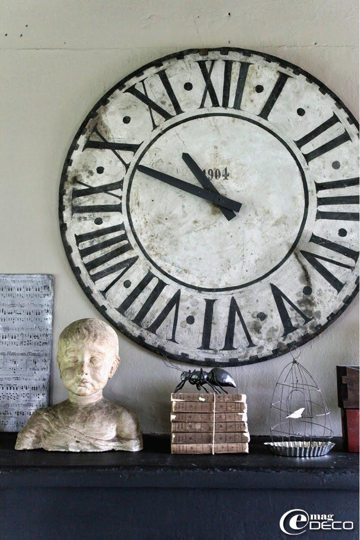 Posés sur la cheminée de la cuisine, un ancien cadran d'horloge, un buste, une pile de livres chinés et une fourmi en papier mâché, création Farfelus Farfadets