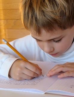 filhos superdotados, menino estudando, criança lendo um livro, criança escrevendo