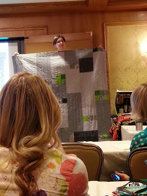 a woman standing on a chair holding a grey quilt and showing it to others
