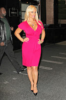 Coco Austin posing on the street in a pink dress