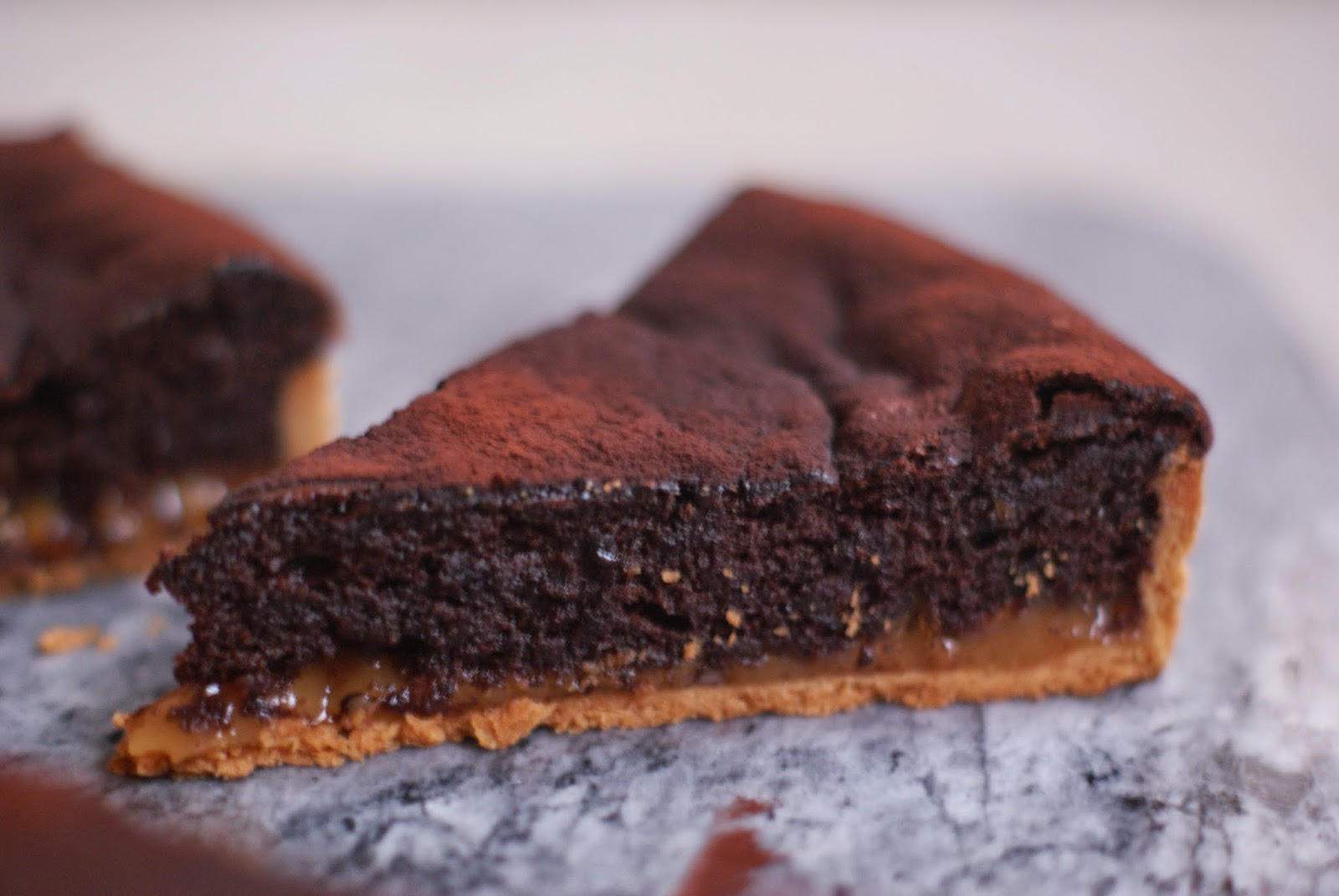 salted caramel, almond and chocolate tart on grey marble