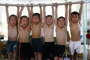 Pain. Chinese children hang up to a bar for 5 minutes during a gymn lesson