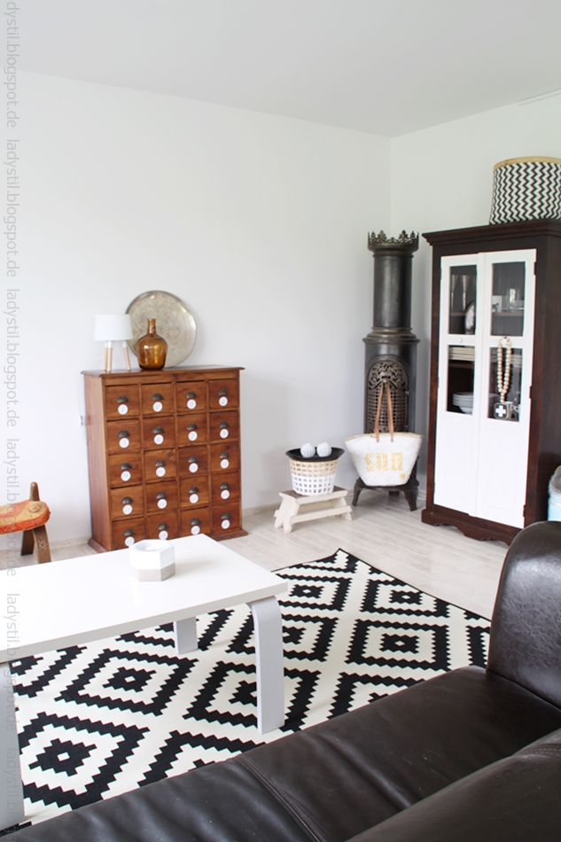 Wohnzimmeransicht mit Vitrine mit weißen Türen, schwarzweißem Teppich und antikem Apothekerschrank