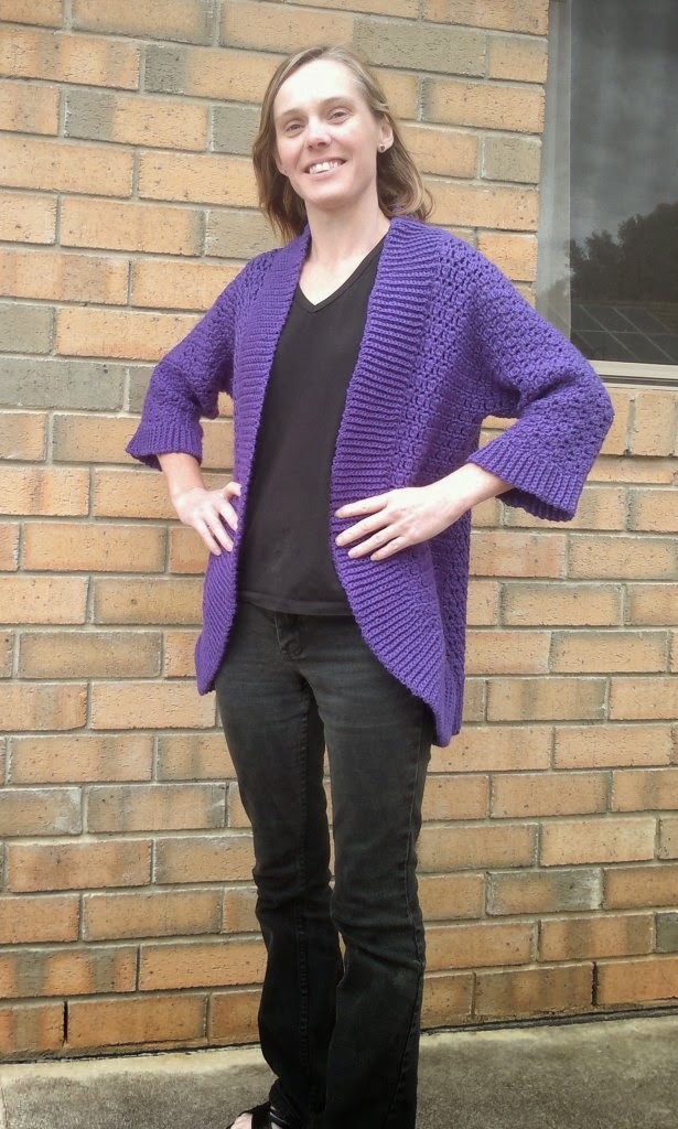 Jodie modelling the front of the purple Belcarra cardigan over black pants and top. Jodie is standing with hands on hips. The cardigan has three-quarter length sleeves with ribbing at the cuffs.  The collar and front edges are ribbed horizontally. This ribbing curves around the bottom front corners to complete the bottom hem.