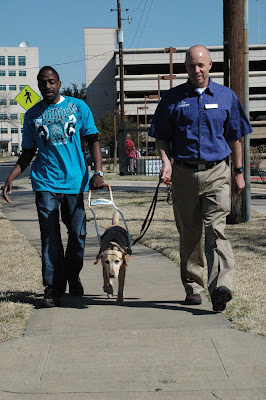 Lifestyles workshop participant working a guide dog with Field Service Manager Bill Archie
