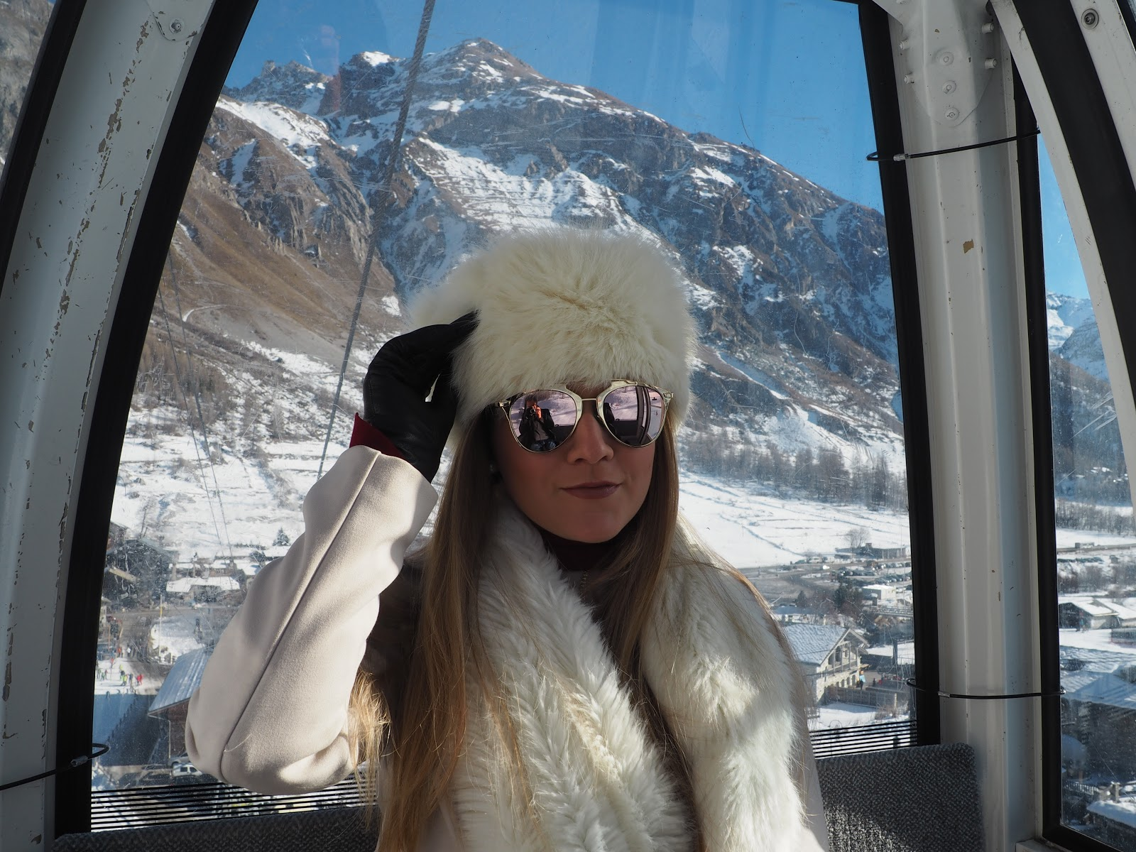 Girl wearing fur hat and scarf and sunglasses in cable car