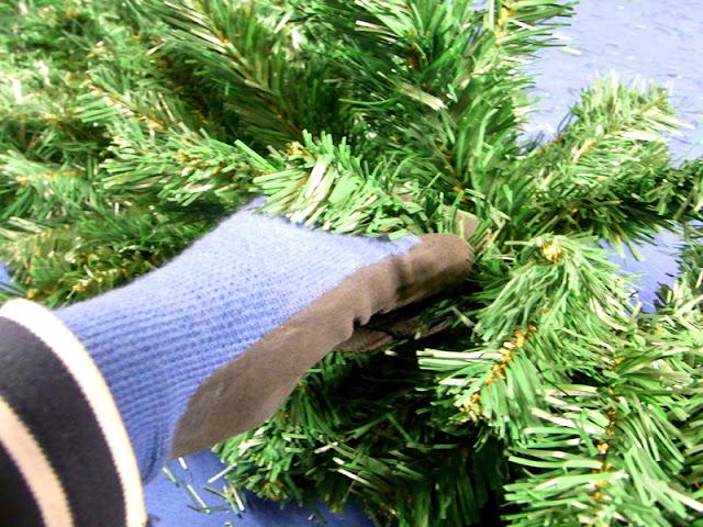 Eine Hand beim Aufrichten von Zweigen, künstliche Weihnachtstannengirlande