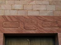 Detall de la llinda gravada sobre la porta, del cos adossat de ponent de Ca n'Oliveres
