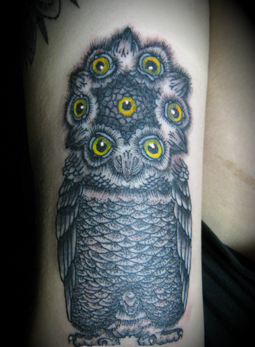 An owl tattoo on the arm with seven eyes around the head.