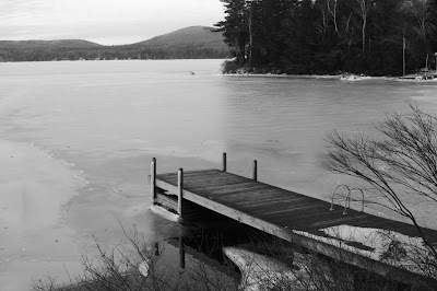 black and white photo of a dock on a frozen lake