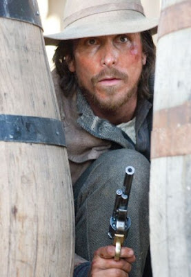 Christian Bale as Dan Evans hiding behind two wooden barrels, gun drawn, intense look on his face in film 3:10 To Yuma (2007)
