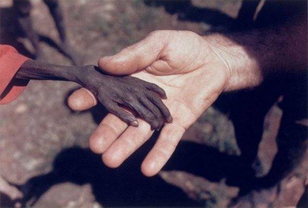 عجائب الدنيا وهل تعلم - بواسطة مايك الآبار، يبين لنا يد طفل أوغندي يمسك بها مبشر. هذه الصورة تضرب لنا مثلا عن مدى التفاوت في هذا العالم.