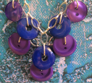 Plunging necklace has layers of purple and blue buttons hanging pendant style from silver chain