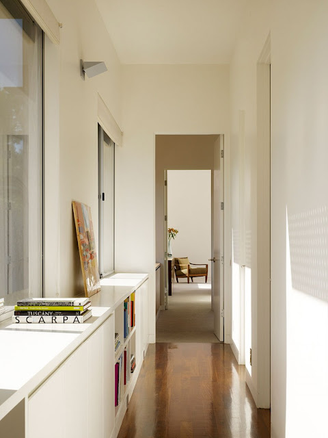 Alleyway in Home with White Bookshelves and White Ceiling above the Brown Floor