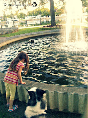 My daughter and my dog posing by the fountain