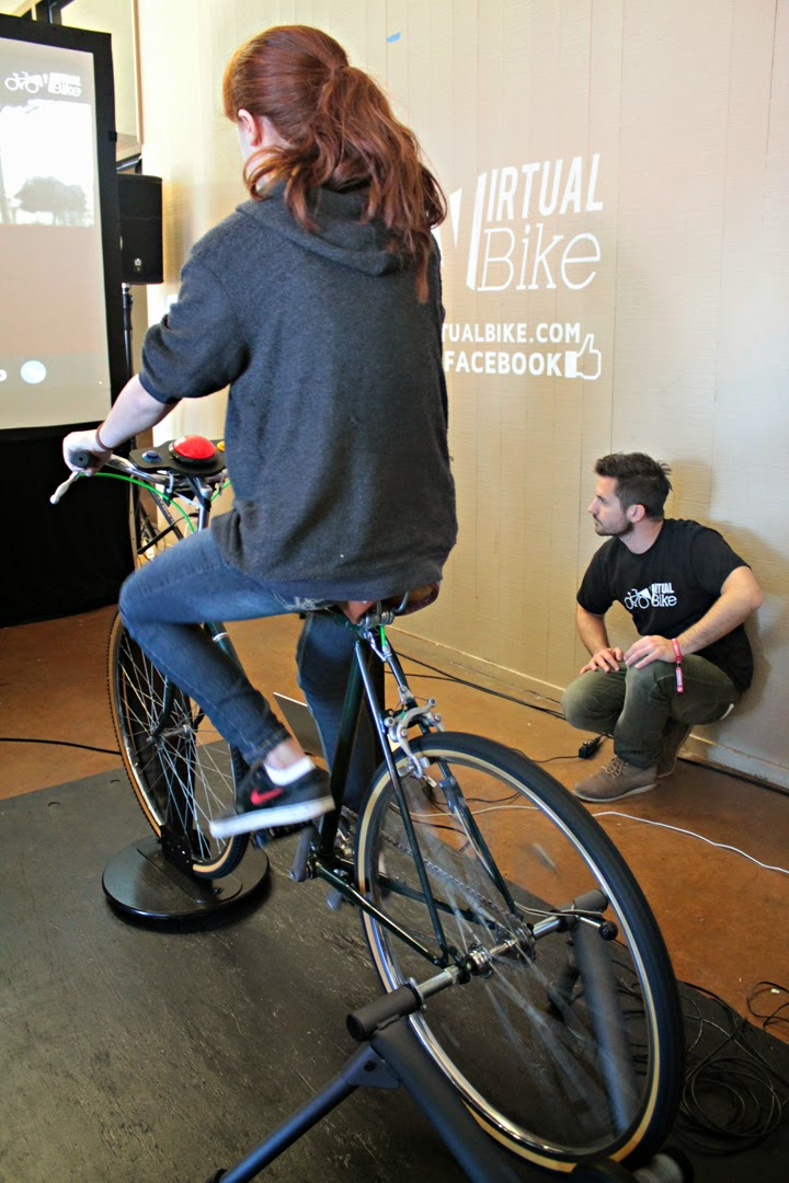 Attendee rides a bike on a virtual tour of Rome as Virtual Bike staffer watches