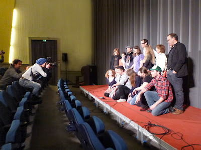 Fotografin steht auf Kinoklappsitz und fotografiert Filmteam