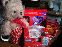 a selection of valentine gifts, a teddy bear, a love mug, chocolate and a mini cake