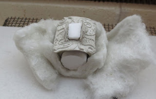 metal clay ring placed in kiln cushioned with fiber pillows. Notice the ring sizing plug.