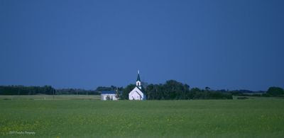 Wide landscape view, deep blue sky, horizon marked by distant green trees, flat land. A small, white church building stands in the center of the frame, with a tall belfry and sharp steeple. The building is flanked on both sides with green trees. A small white house, perhaps the parsonage, peeks from behind the trees on the left side. The image evokes peaceful, quiet faith. Is the faith in the building, in the power of peace, or in their God?