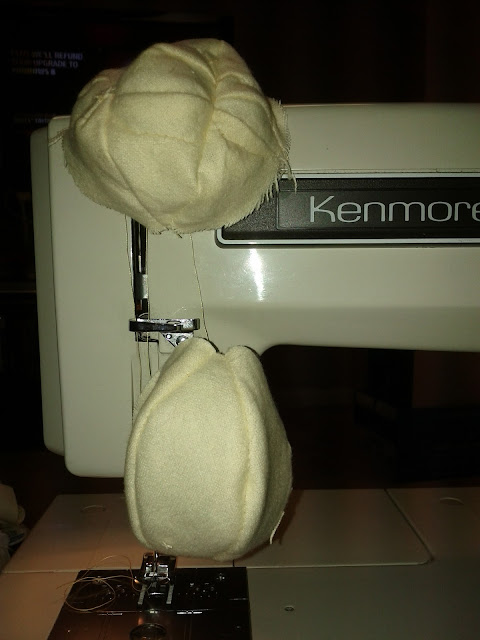 Two halves of a ball of yellow fabric are complete and hang from the sewing machine.  One has a nose and cheeks on it.