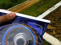Close de uma aba de plástico que tem na ponta da bolsa plástica, para lacrar a embalagem.