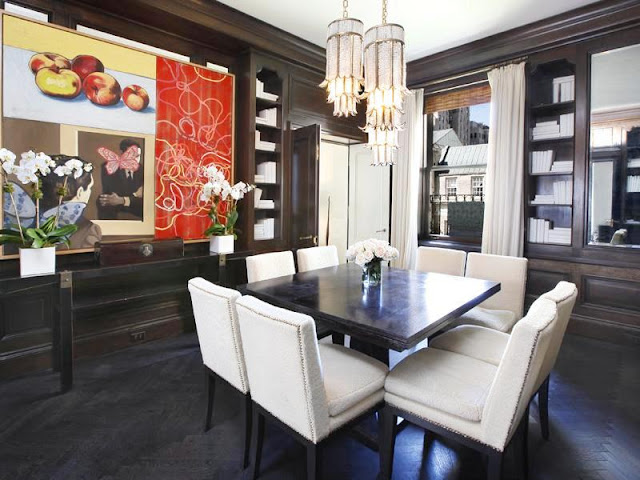 Dining room in an apartment with grey herringbone wood floor, a square table surrounded by white chairs, built in grey wood bookcase and two crystal flower pendant lights