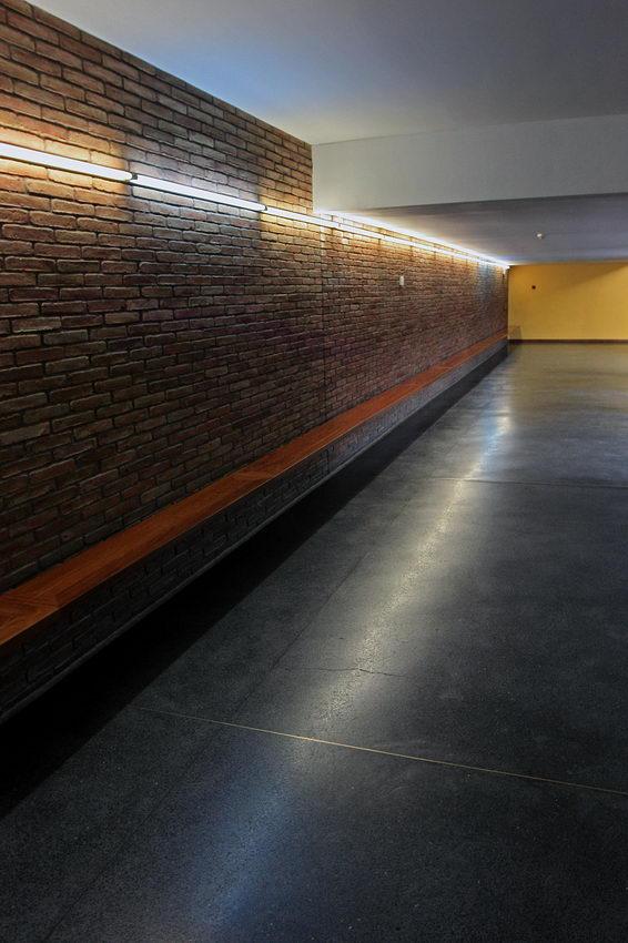 Pormenor dum coredor com uma parede revestida a pedra, do lado esquerdo, com uma linha de lâmpadas fluorescentes na parte superior e um banco ao longo desta parede
