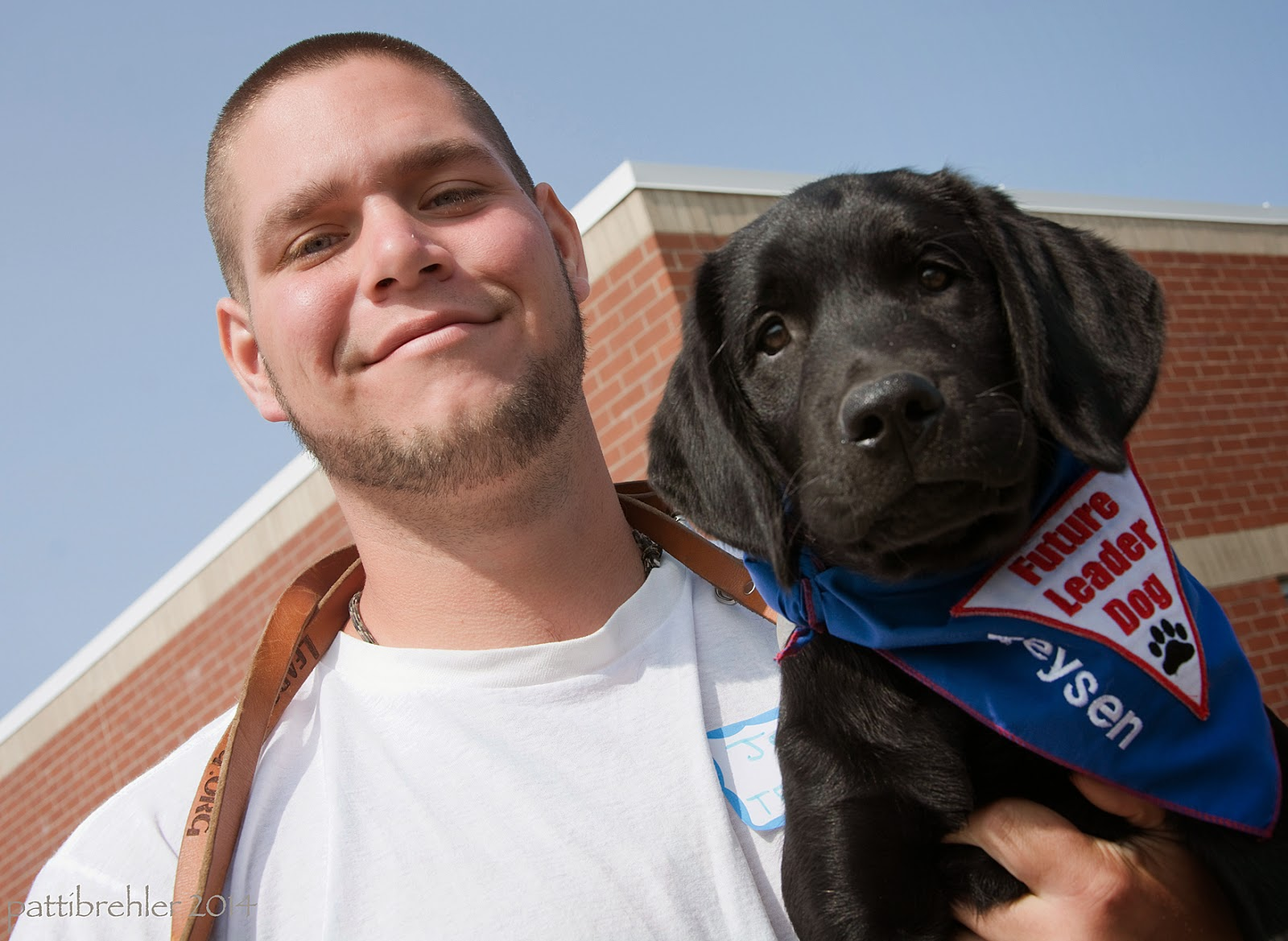 "An upwards looking shot of a young man dressed in a white t-shirt holding a small black lab in his left arm. The man has a big grin on his face and the leash looped around his neck. The puppy is wearing a blue Future Leader Dog bandana with the name ""Teysen"" embroidered in white on it, he is looking at the camera. The sky behind them is deep blue and there is a brick building behind them too."