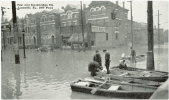 people standing looking at the high water with buildings flooded in the background