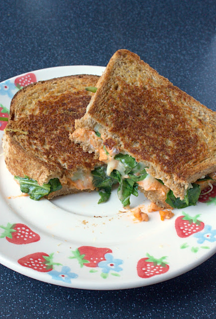 A toastie or Grilled Cheese Sandwich packed with cream cheese, Cheddar, spinach and homemade sundried tomato hummus.